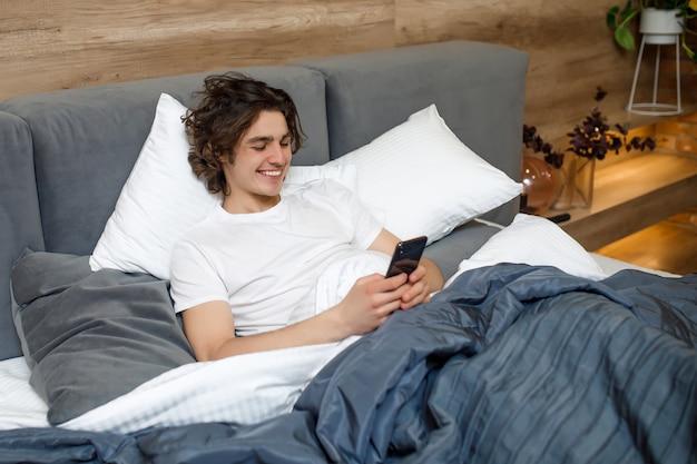 Beau jeune homme en pyjama à l'aide d'un téléphone portable en position couchée dans son lit le matin
