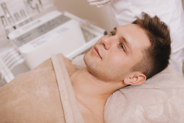 Beau jeune homme recevant un traitement de soin de la peau au salon de beauté