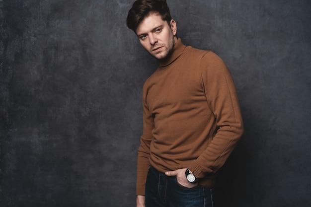 Beau jeune homme à la recherche. portrait de jeune homme avec les mains dans les poches appuyé contre le mur gris.