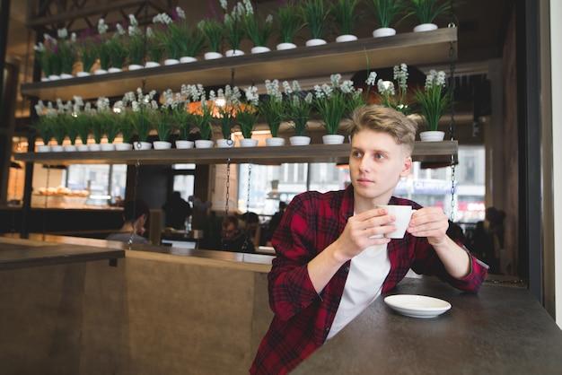 Un beau jeune homme réfléchi, assis dans un café, boire du café et regarder ailleurs.