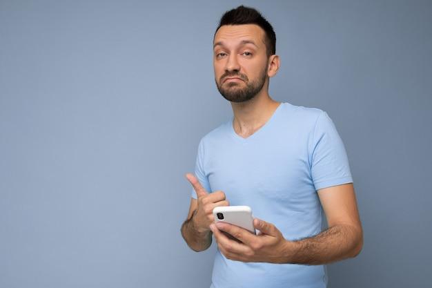 Un beau jeune homme réfléchi isolé sur un mur de fond portant des vêtements de tous les jours tenant et utilisant un téléphone portable en écrivant des sms en regardant la caméra et en pensant