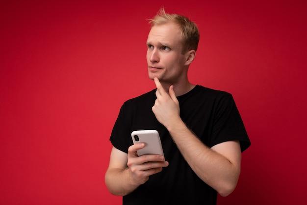 Un beau jeune homme réfléchi isolé sur un mur de fond portant des vêtements de tous les jours tenant et utilisant un téléphone portable en écrivant des sms en regardant sur le côté.