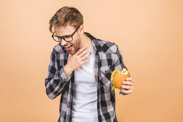 Beau jeune homme refusant un burger malsain