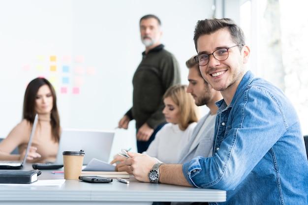 Beau jeune homme regardant la caméra et souriant pendant que ses collègues travaillent en arrière-plan