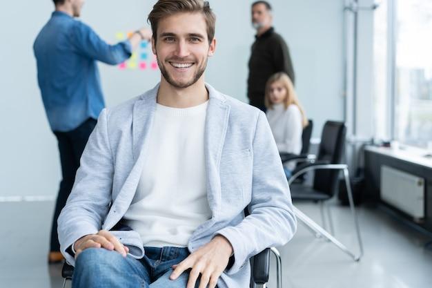 Beau jeune homme regardant la caméra et souriant