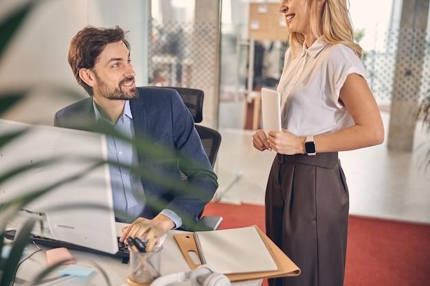 Beau jeune homme regardant une charmante dame et souriant tout en étant assis à la table avec un ordinateur au bureau