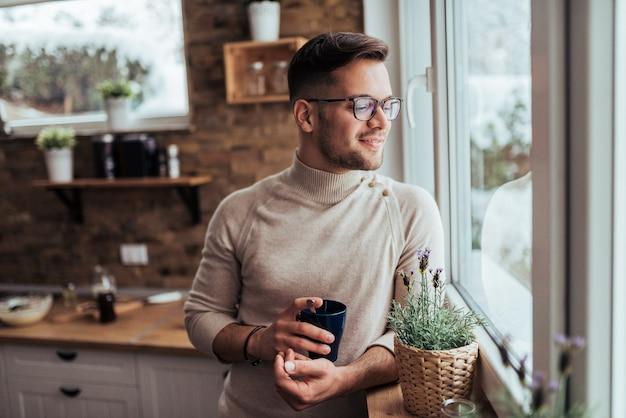 Beau jeune homme regardant à travers une maison confortable et buvant du thé ou du café.