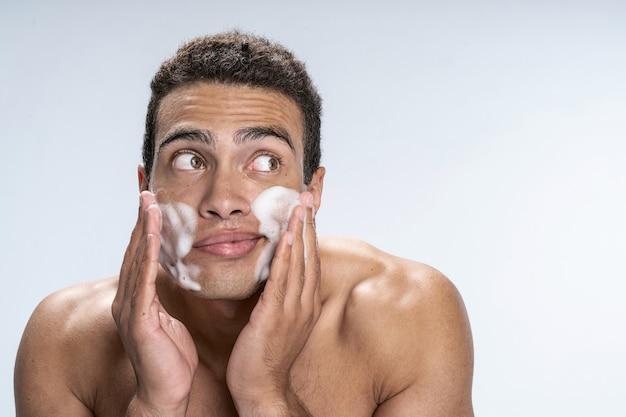Beau jeune homme répandant de la mousse nettoyante et détournant les yeux