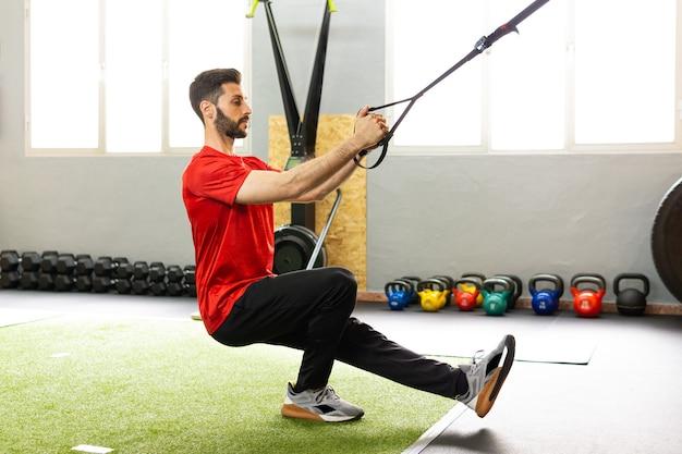 Beau jeune homme s'entraînant dans la salle de sport avec trx fitness