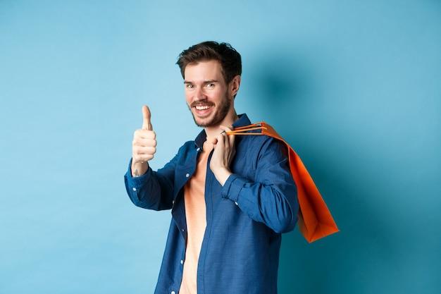 Beau jeune homme avec sac à provisions montrant les pouces vers le haut et souriant, louant une bonne offre de promotion, debout sur fond bleu.