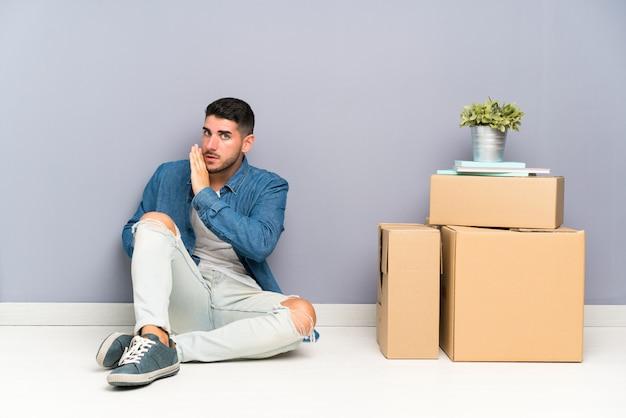 Beau jeune homme se déplaçant dans la nouvelle maison parmi les boîtes chuchotant quelque chose