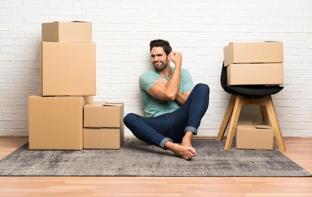 Beau jeune homme se déplaçant dans la nouvelle maison parmi les boîtes faisant un geste fort
