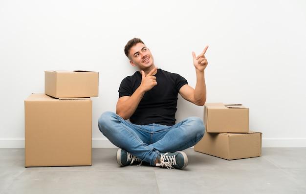 Beau jeune homme se déplaçant dans la nouvelle maison parmi les boîtes de pointage
