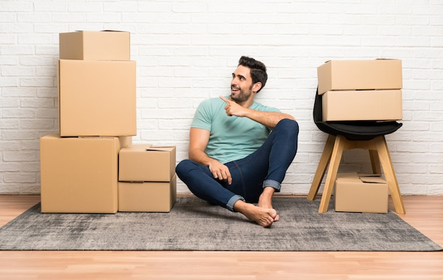 Beau jeune homme se déplaçant dans la nouvelle maison parmi les boîtes pointant le doigt sur le côté