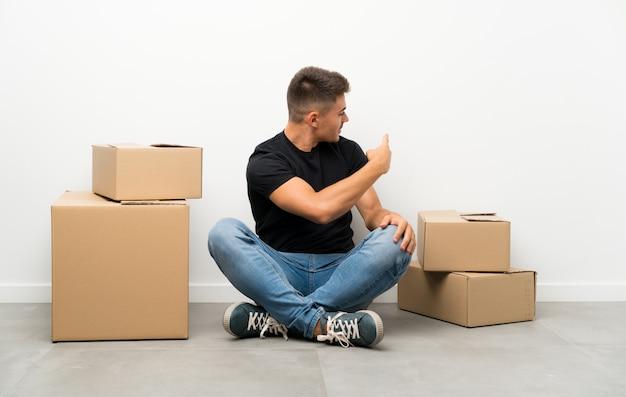 Beau jeune homme se déplaçant dans la nouvelle maison parmi les boîtes pointant vers l'arrière avec l'index