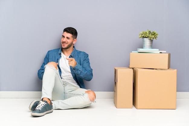 Beau jeune homme se déplaçant dans la nouvelle maison parmi les boîtes pointe le doigt vers vous