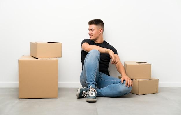 Beau jeune homme se déplaçant dans la nouvelle maison parmi les boîtes à la recherche sur le côté