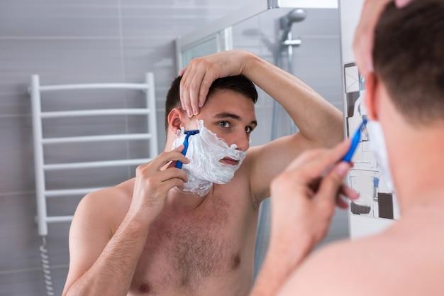 Beau jeune homme se rasant le visage avec un rasoir et regardant le miroir dans la salle de bain carrelée moderne à la maison