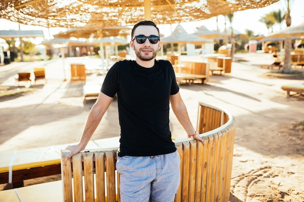 Beau jeune homme se reposant au restaurant de plage en bord de mer