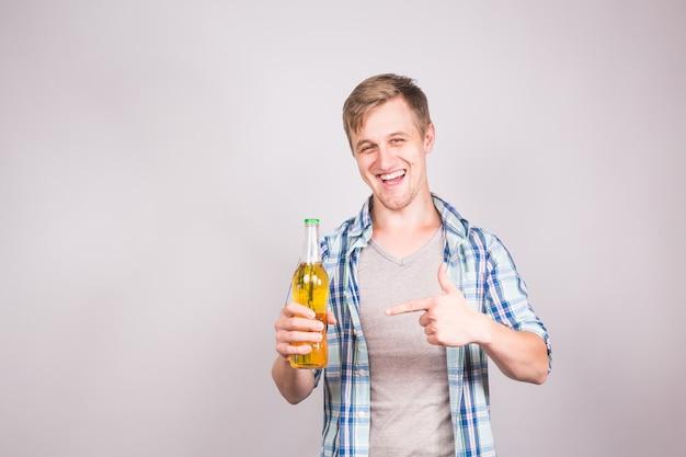 Un beau jeune homme se sentant heureux en montrant les pouces vers le haut et tenant une bouteille de bière.