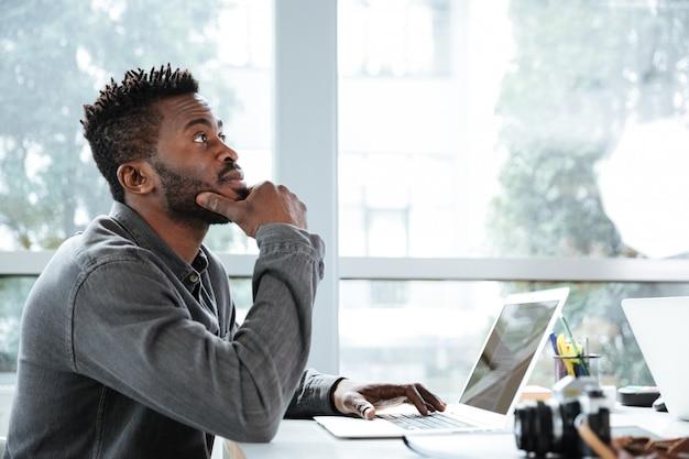 Beau jeune homme sérieux pensant assis dans le coworking de bureau