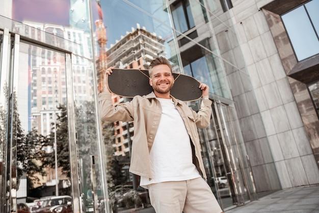 Beau jeune homme souriant blond tenant une planche à roulettes sur les épaules dans la rue de la ville, debout parmi les bâtiments en verre. porte une tenue en jean. skateur sportif et élégant pensant à un tour extrême à l'extérieur.