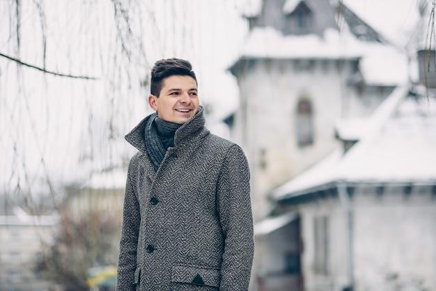 Un beau jeune homme souriant dans un manteau chaud et des gants de cuir en marchant sur la ville