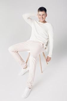 Beau jeune homme souriant dans un pull blanc et un pantalon sur fond blanc