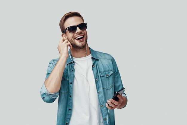 Beau jeune homme souriant et écoutant de la musique en se tenant debout sur fond gris