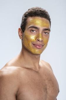 Beau jeune homme souriant avec un masque facial spécial