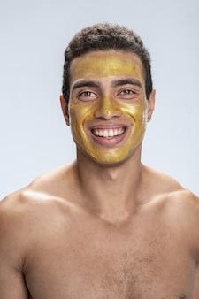 Beau jeune homme souriant avec un masque facial