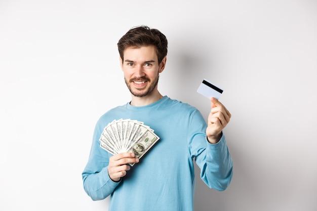 Beau jeune homme souriant et offrant un paiement en espèces et sans contact, montrant de l'argent avec une carte de crédit en plastique, debout sur fond blanc.
