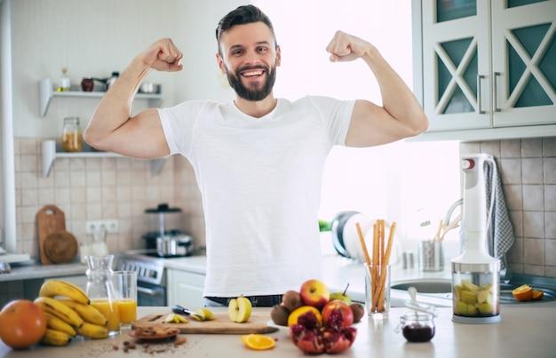 Beau jeune homme souriant sportif dans la cuisine avec des fruits. concept d'alimentation saine