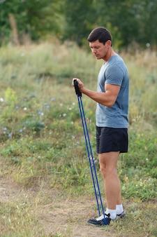Beau jeune homme sportif musclé exerçant à l'extérieur en plein air avec un élastique. fit, fitness, exercice, entraînement et concept de mode de vie sain.