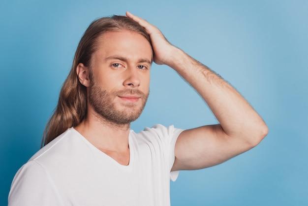 Beau jeune homme en t-shirt blanc isolé sur fond bleu toucher la tête concept de soins capillaires
