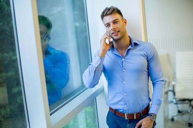 Beau jeune homme avec un téléphone portable au bureau