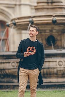 Beau jeune homme tenant un bretzel et se détendre dans le parc