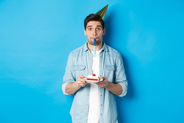 Beau jeune homme tenant un gâteau d'anniversaire, portant un chapeau de fête et un coup de sifflet, debout sur un mur bleu