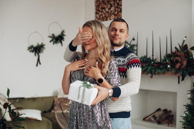 Beau jeune homme tenant la main sur ses yeux de petite amie tout en lui donnant un cadeau de noël spécial