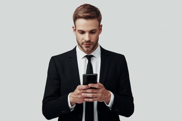 Beau jeune homme en tenue de soirée à l'aide d'un téléphone intelligent en se tenant debout sur fond gris