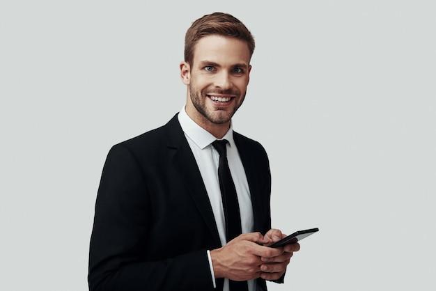 Beau jeune homme en tenue de soirée à l'aide d'un téléphone intelligent et souriant en se tenant debout sur fond gris