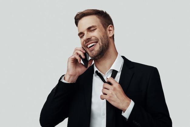 Beau jeune homme en tenue de soirée parlant au téléphone et souriant en se tenant debout sur fond gris