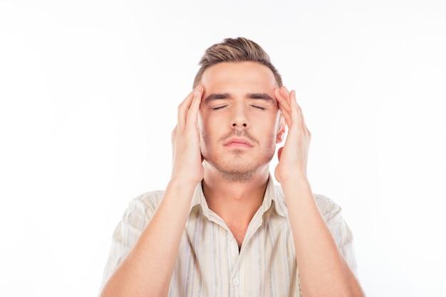 Beau jeune homme touchant sa tête souffrant de maux de tête