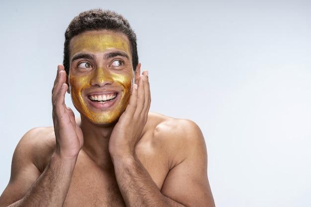 Beau jeune homme touchant ses joues avec un masque facial
