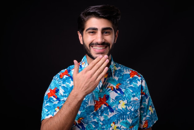Beau jeune homme touriste persan barbu prêt pour des vacances sur fond noir