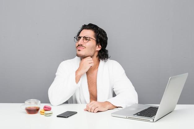 Beau jeune homme travaillant après une douche souffre de douleurs à la gorge en raison d'un virus ou d'une infection.