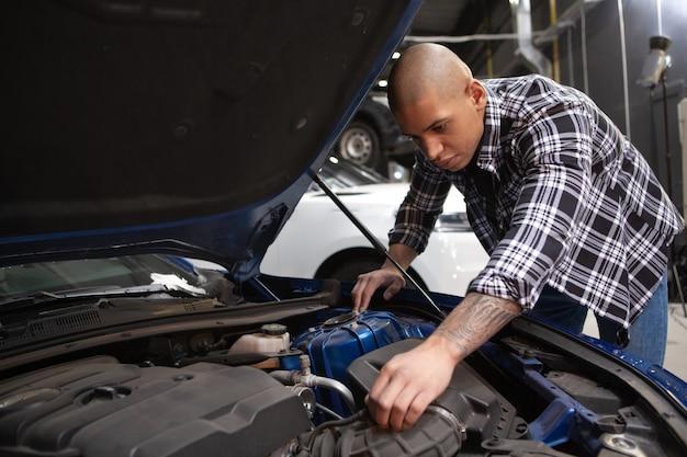 Beau jeune homme travaillant dans son garage