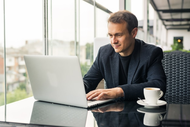 Beau jeune homme travaillant sur ordinateur portable et souriant alors qu'il était assis dans un café-terrasse