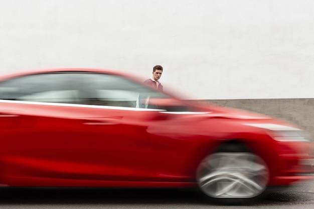 Beau jeune homme urbain à la mode avec une coiffure en veste en jean bleu à la mode à pied près d'un bâtiment blanc vintage en ville. un mec élégant en jeans décontractés marche dans la rue près de la route avec une voiture rouge.