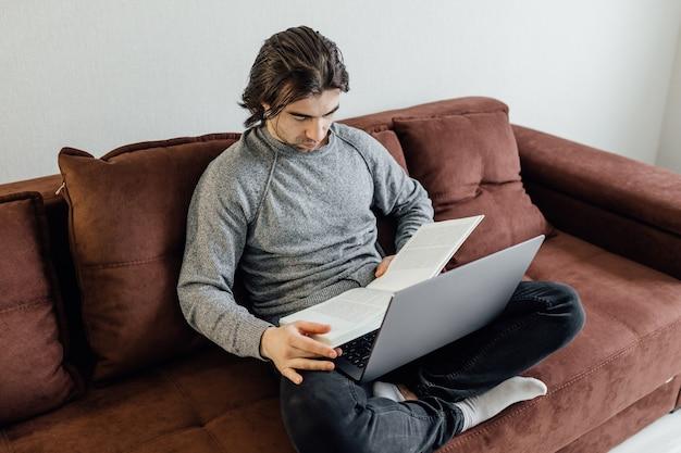Beau jeune homme utilisant un ordinateur portable à la maison. l'homme étudiant lit le livre. achats en ligne, travail à domicile, indépendant, apprentissage en ligne, concept d'étude. l'enseignement à distance